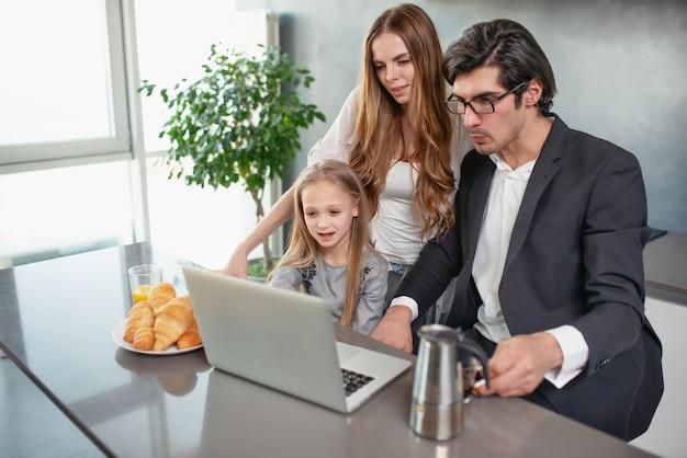 Gelukkig meisje kijken naar een film op de computer met haar vader en moeder thuis