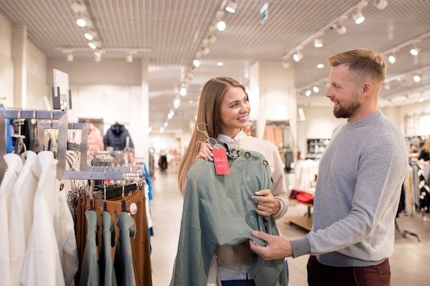 Gelukkig meisje kijkt naar haar vriendje terwijl wijzend op grijze gebreide pullover op hanger bij de borst tijdens het winkelen in het winkelcentrum