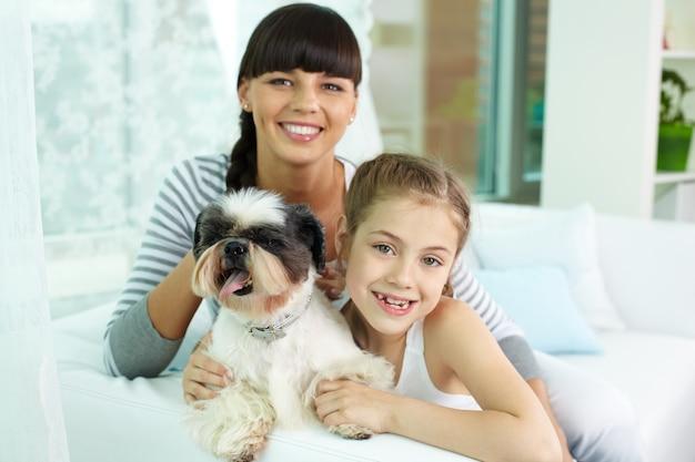 Gelukkig meisje knuffelen de hond met haar moeder