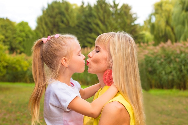 Gelukkig meisje knuffelen en zoenen haar moeder