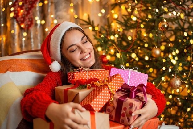 Gelukkig meisje knuffelt een grote stapel cadeautjes