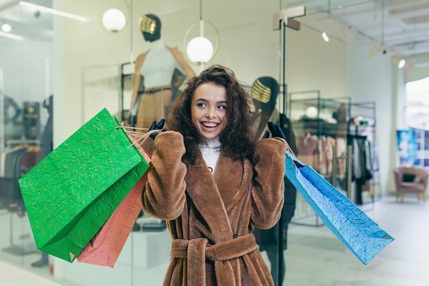 Gelukkig meisje komt uit een kledingwinkel, met tassen met goederen