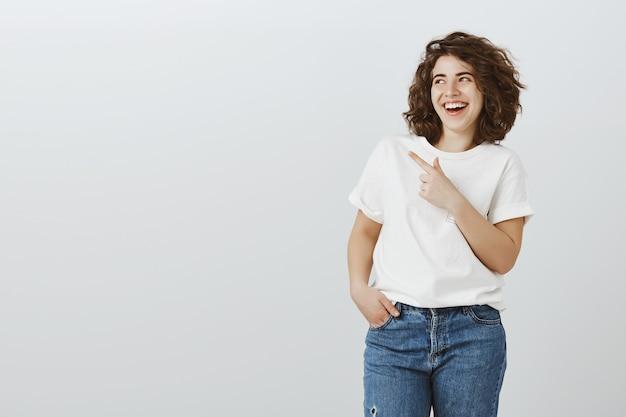 Gelukkig meisje lachen en glimlachen, wijzende vinger linker bovenhoek grappige advertentie