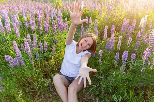 Gelukkig meisje lachend buiten. mooie jonge brunette vrouw rusten op zomer veld met bloeiende wilde bloemen. gratis gelukkige europese vrouw. positieve menselijke emotie gezichtsuitdrukking.