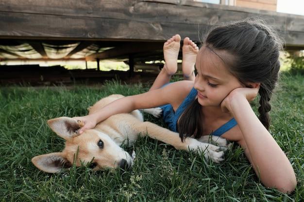 Gelukkig meisje liggend op groen gras en haar hond buitenshuis aaien