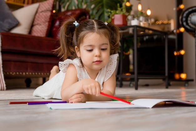 Gelukkig meisje ligt op de vloer van het huis en tekent met kleurpotloden. ontwikkeling van het kind. blijf thuis