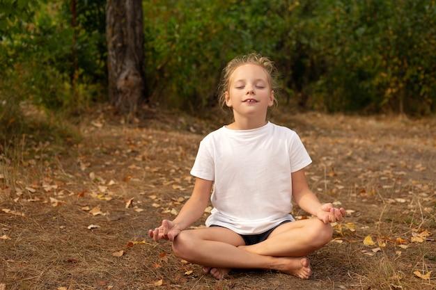 Gelukkig meisje mediteert op groen veld op zonnige zomerdag