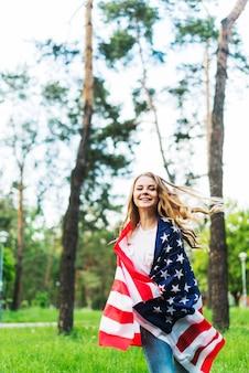 Gelukkig meisje met amerikaanse vlag in de natuur