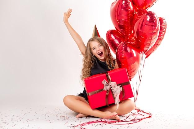 Gelukkig meisje met armvol ballen in de vorm van harten en een pet voor haar verjaardag.