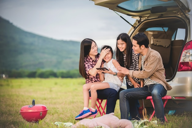 Gelukkig meisje met aziatische familiezitting in de auto om van wegreis en de zomervakantie i te genieten