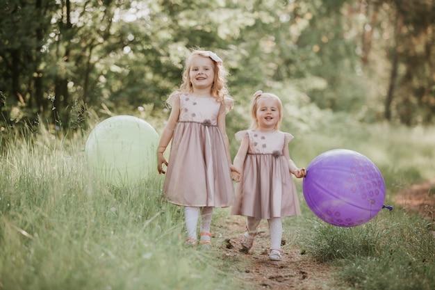 Gelukkig meisje met ballonnen. twee mooie kleine meisjes in de zomer in een park met ballonnen in handen.