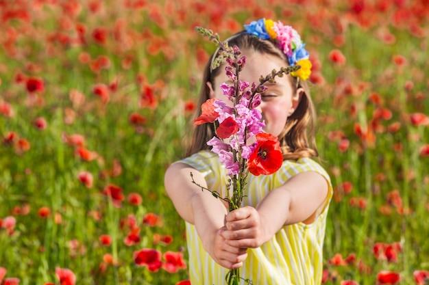 Gelukkig meisje met bloeiende bloemen in veld