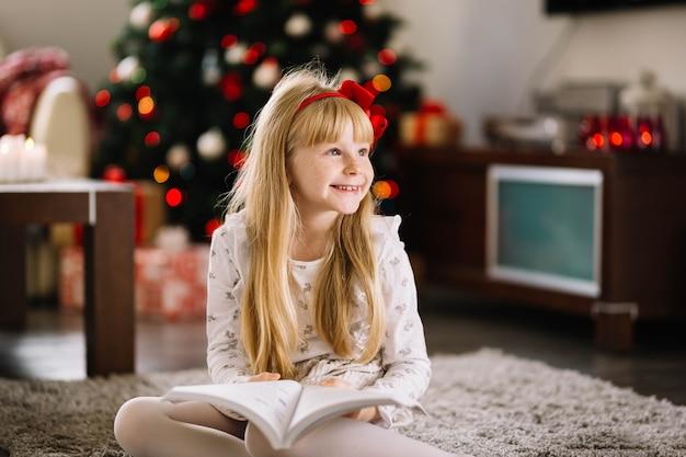 Gelukkig meisje met boek voor kerstboom
