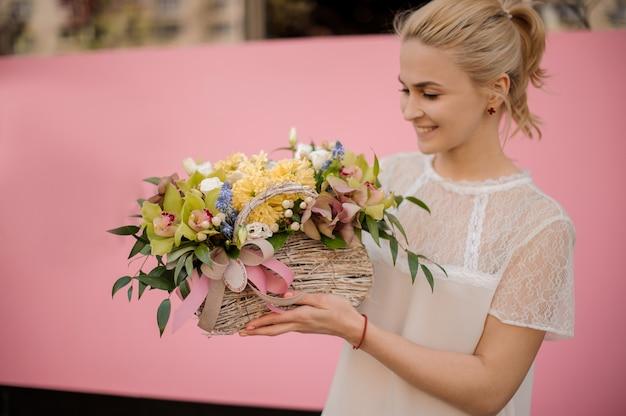 Gelukkig meisje met boeket in bloemmand