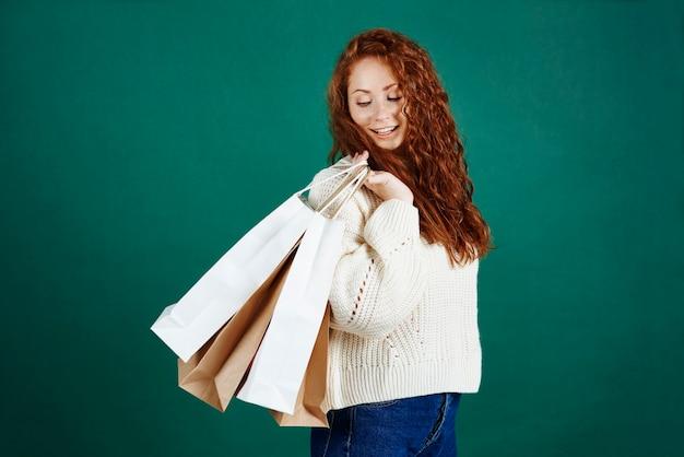 Gelukkig meisje met boodschappentassen bij studio-opname