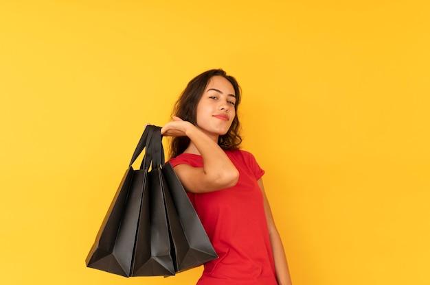 Gelukkig meisje met boodschappentassen op achtergrond in kleur