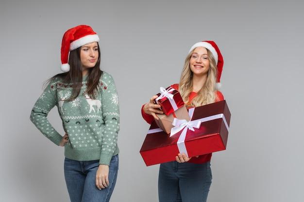 Gelukkig meisje met cadeautjes en ongelukkig meisje met niets