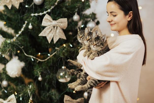 Gelukkig meisje met drie schattige kittens met kerstboom