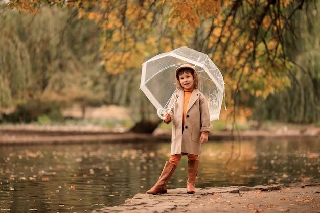 Gelukkig meisje met een doorzichtige paraplu op een wandeling in de herfst aan het meer