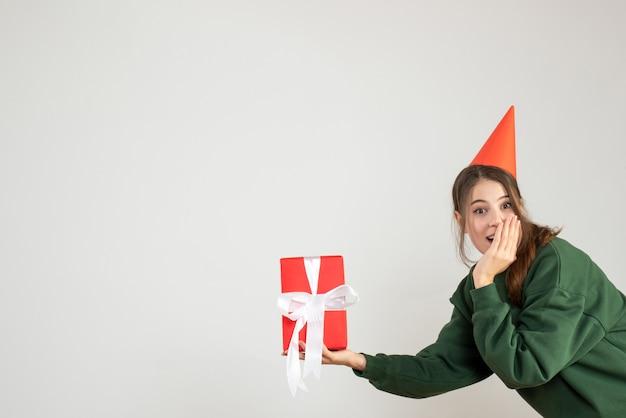 Gelukkig meisje met een feestmuts met kerstcadeau op wit