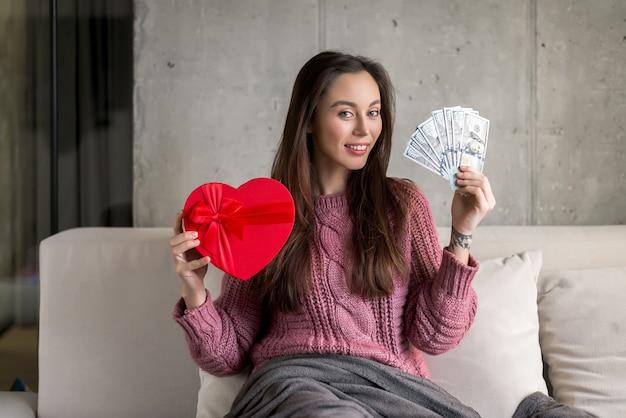 Gelukkig meisje met een hartvormige geschenk en dollarbiljetten