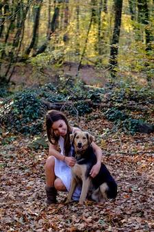 Gelukkig meisje met een hond in een beukenbos. herfstseizoen
