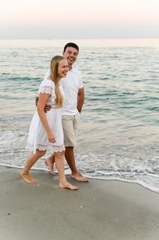 Gelukkig meisje met een jongen knuffel tijdens een wandeling langs het strand in de buurt van de oceaan. romantische wandeling. man en vrouw lachen en knuffelen bij de zee.