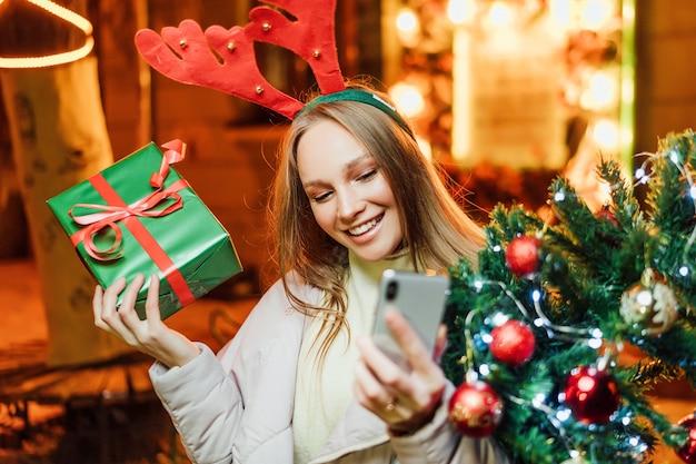Gelukkig meisje met een kerstboom en een cadeau in haar handen praat en glimlacht aan de telefoon