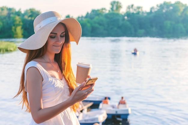 Gelukkig meisje met een smartphone met koffie in haar handen. tegen de achtergrond van water van boten en catamarans.