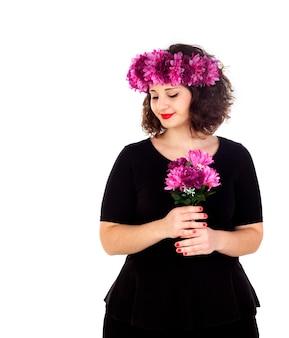 Gelukkig meisje met een tak en een kroon met roze en purpere bloemen