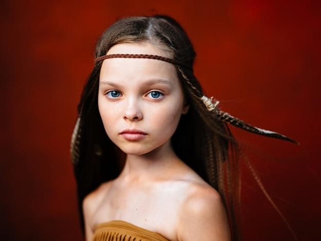 Gelukkig meisje met een veer in haar haar aboriginals indiase stam sjamaan rode achtergrond
