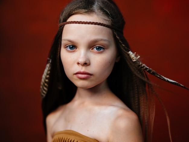 Gelukkig meisje met een veer in haar haar inboorlingen indische stam sjamaan rood