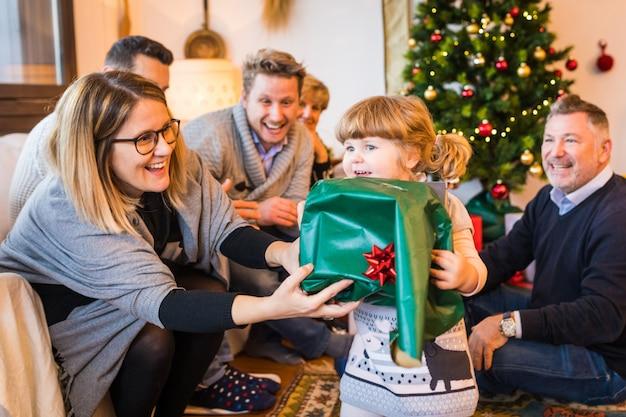 Gelukkig meisje met familie unboxing gift op eerste kerstdag