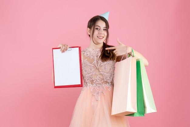 Gelukkig meisje met feestmuts met documenten en boodschappentassen op roze