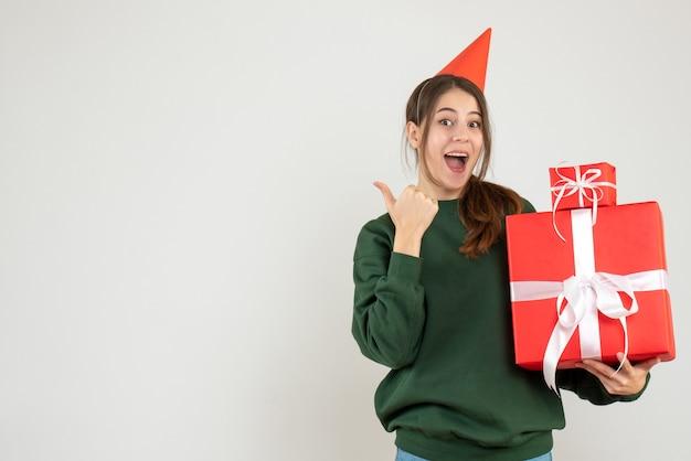 Gelukkig meisje met feestmuts wijzend op iets met geschenken op wit