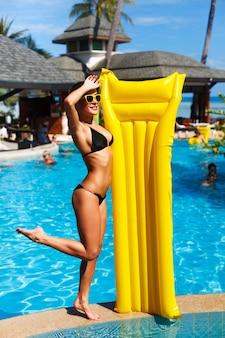 Gelukkig meisje met gele luchtbed dicht bij het zwembad