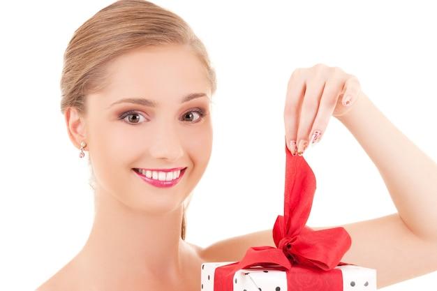 Gelukkig meisje met geschenkdoos over witte muur