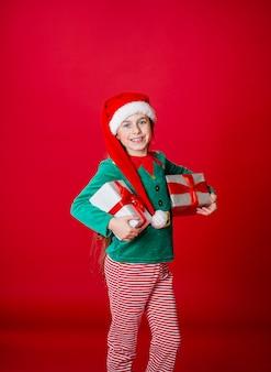 Gelukkig meisje met geschenken in een kostuum van santa claus helper elf op een fel rood