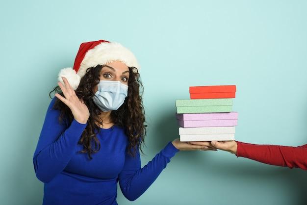 Gelukkig meisje met gezichtsmasker ontvangt kerstcadeaus.