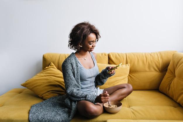 Gelukkig meisje met gezond ontbijt, havermout, muesli, luisteren muziek in oortelefoons op gele sofa thuis. ze heeft kort krullend haar, draagt een grijs lang vest, korte broek.