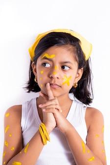 Gelukkig meisje, met haar gezicht geschilderd om de gele dag te vieren