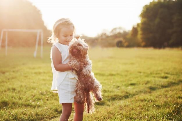Gelukkig meisje met haar hond in het park bij zonsondergang