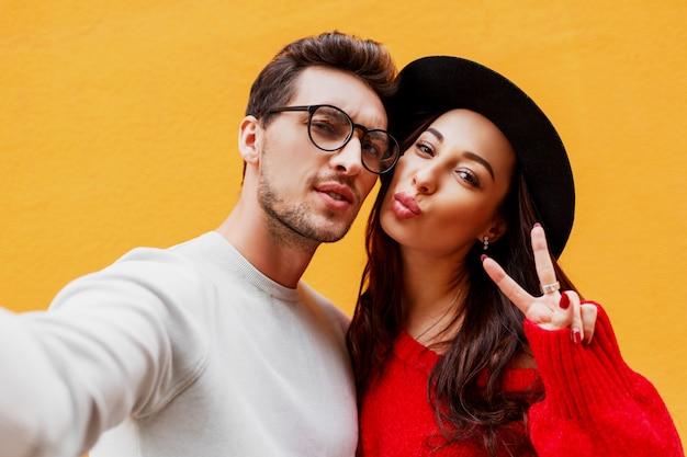 Gelukkig meisje met haar vriend die zelfportret maken door mobiele telefoon. gele muur. het dragen van rode gebreide trui. nieuwjaarsfeeststemming.
