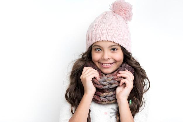 Gelukkig meisje met handen op sjaal van nek