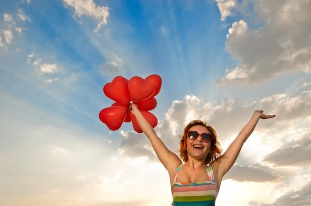 Gelukkig meisje met hartvormige balonnen