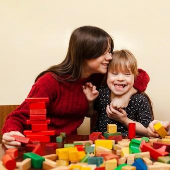 Gelukkig meisje met het syndroom van down en speelgoed