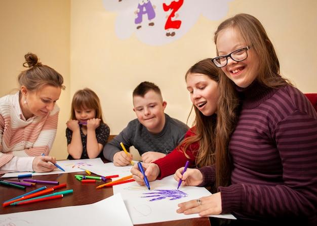 Gelukkig meisje met het syndroom van down poseren tijdens het tekenen