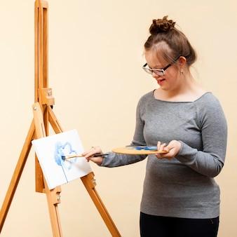 Gelukkig meisje met het syndroom van down schilderen