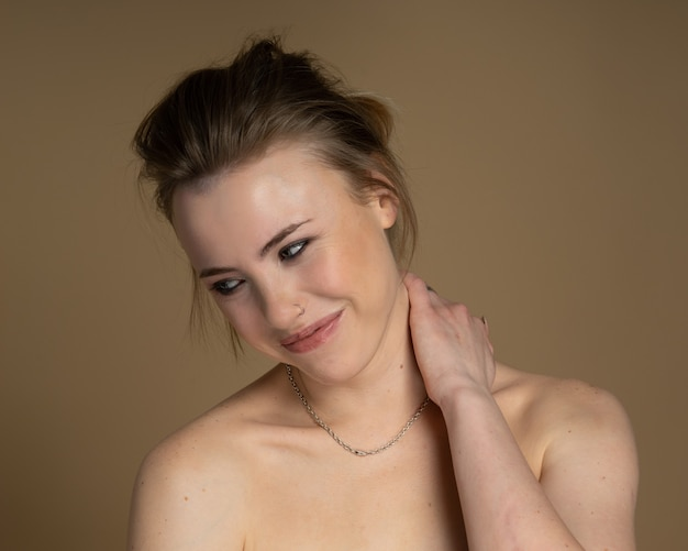 Gelukkig meisje met heterochromie, neuspiercing en plug in één oor, en vreemd kapsel. met geweldige professionele make-up en zilveren ketting om haar nek. beige achtergrond. studio opname