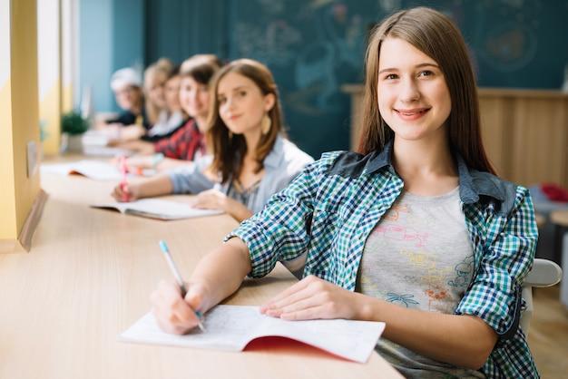 Gelukkig meisje met klasgenoten aan tafel